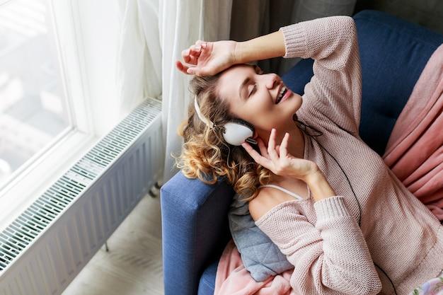 Wunderbare frau mit lockigen kurzen haaren hört lieblingsmusik und liegt mit geschlossenen augen vor vergnügen. tragen niedliche rosa loungewear.