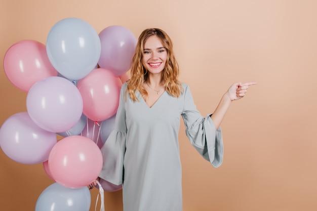 Wunderbare geburtstagsfrau, die mit lächeln aufwirft und helle luftballons hält