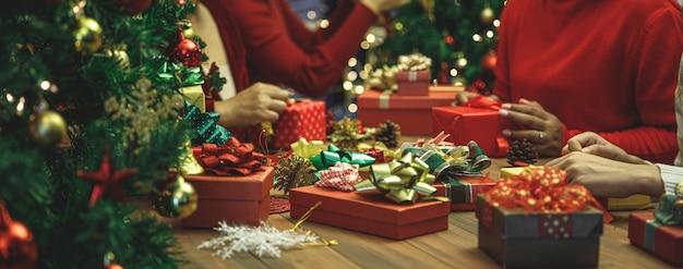 Wunderbare geschenkboxen mit farbenfroher, charmanter schleife auf dem tisch bei der weihnachtsfeier. familienfrauen geben gerne ein geschenk, um warme liebe an einem schönen feiertag zu teilen. fügen sie etwas rauschen hinzu, um das bild im vintage-stil anzupassen.