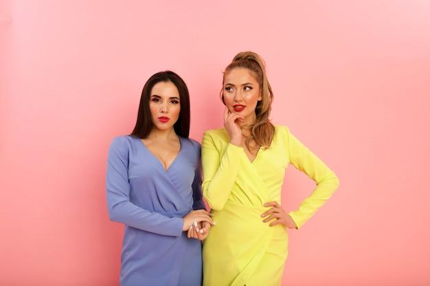 Wunderbare helle damen in sommerlichen modischen kleidern, gelb und blau. blond und brünett mit großen roten lippen und moderner frisur. formschön heiße körper, sexy models. shooting im studio auf dem pin-hintergrund