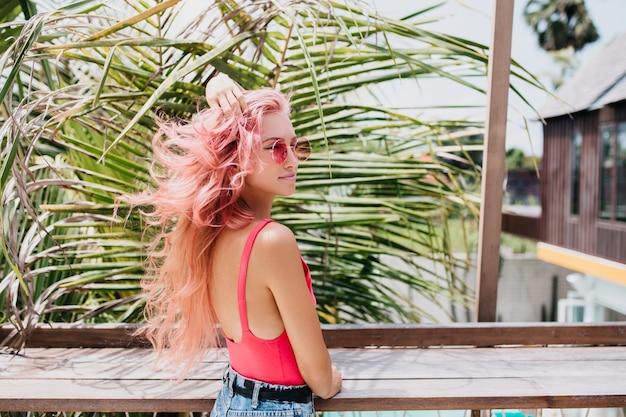 Wunderbare junge frau im stilvollen sommeroutfit, das auf exotischem hintergrund aufwirft.