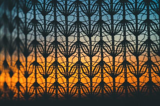 Wunderbare lebendige morgendämmerung vom fenster durch gemusterten vorhang. erstaunlich warmer himmel hinter silhouetten der tüllbeschaffenheit.