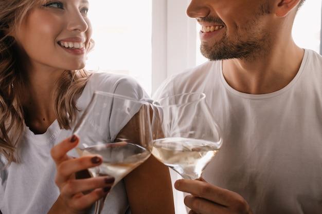 Wunderbare lockige frau, die jubiläum mit freund feiert. paar trinkt champagner.