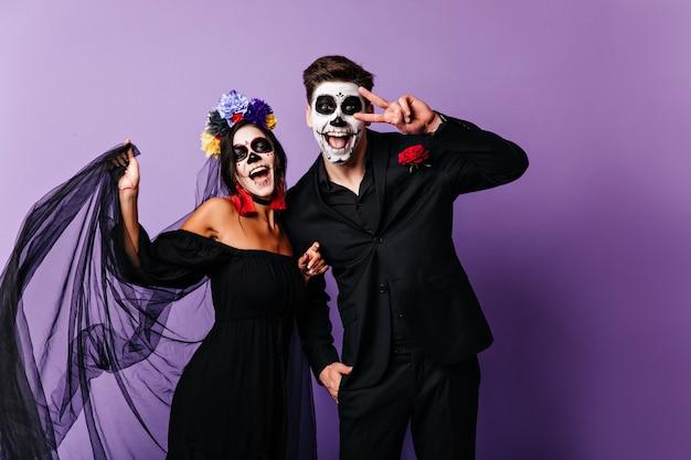 Wunderbare mexikanische zombies, die glück ausdrücken. charmantes muerte-mädchen, das halloween mit freund feiert.