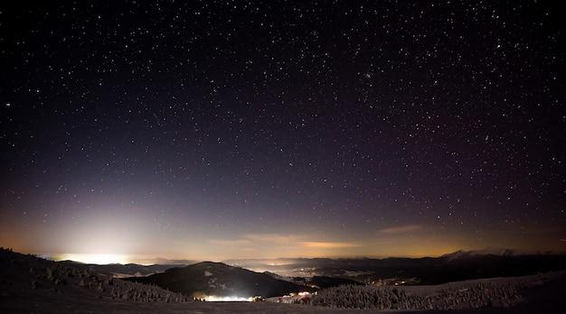 Wunderbare nachtansicht des skigebiets mit hügeln und pisten vor dem hintergrund des mondes und des sternenhimmels. das konzept des wintersports und der erholung im freien. copyspace