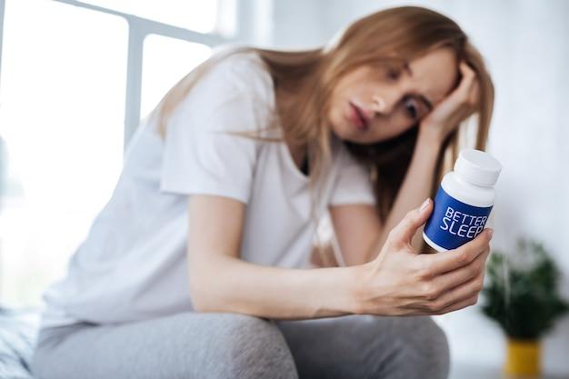 Wunderbare pillen. unglückliche blonde frau, die sitzt und ihre schlaftabletten betrachtet
