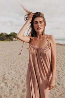Wunderbare stilvolle frau mit langen haaren, die langes kleid tragen, das beim gehen auf dem strand posiert