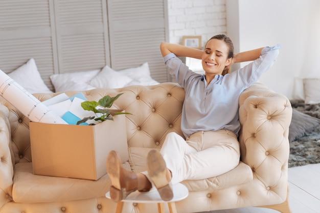 Wunderbare stimmung. fröhliche, positiv lächelnde frau, die sich beim entspannen auf dem sofa nach dem ersten tag bei ihrer neuen arbeit gut fühlt