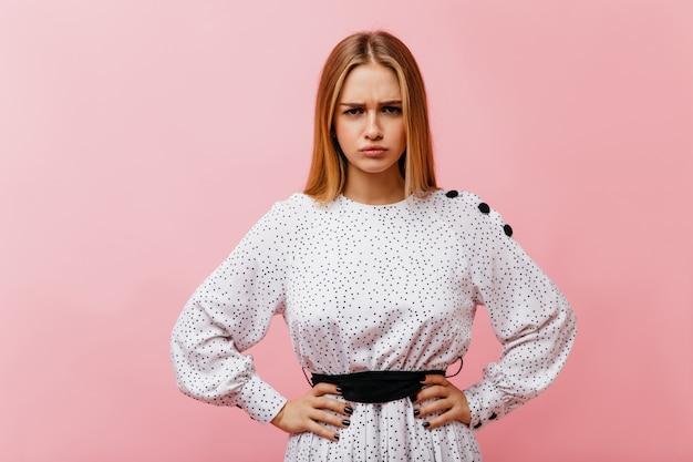 Wunderbare weiße frau mit glattem haar, das auf hellrosa backgorund steht. innenporträt der ernsten glamourösen frau in der eleganten bluse.