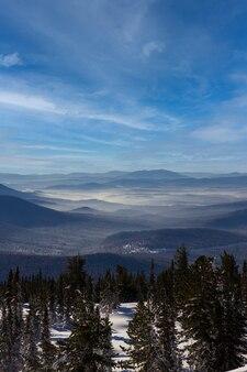Wunderbare wintergebirgslandschaft an einem sonnigen tag. berge in der ferne im nebel.