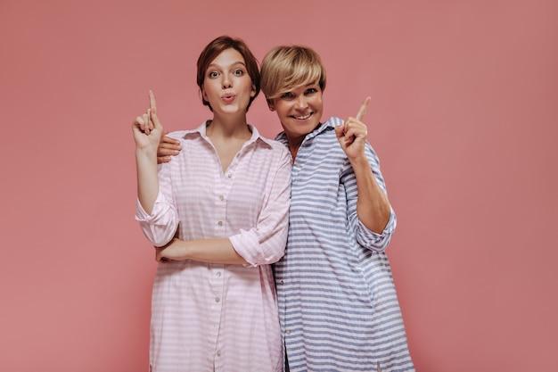 Wunderbare zwei frauen mit stilvoller kurzer frisur in gestreiften sommerkleidern, die sich umarmen und zeigen, um für text auf rosa hintergrund zu platzieren.