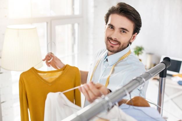 Wunderbarer blick. ich bin froh, dass der bärtige stylist lächelt und die pullover in seiner sammlung betrachtet
