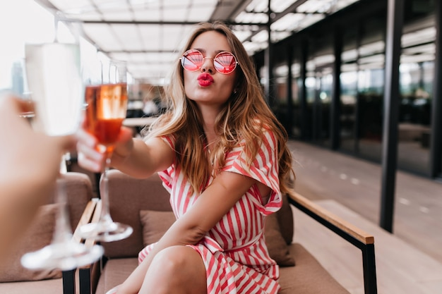 Wunderbarer junger weiblicher modelltrinkcocktail im restaurant. innenaufnahme des romantischen mädchens im gestreiften kleid, das mit küssendem gesichtsausdruck im café aufwirft.