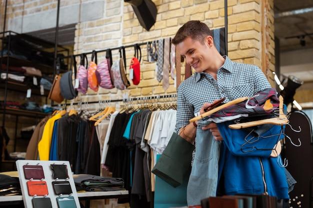 Wunderbarer rabatt. fröhlicher junger mann, der lächelt und große menge an kleidern hält, während er modischen laden besucht und lederbrieftaschen betrachtet