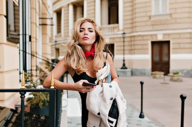 Wunderbares blondes mädchen mit stilvollem haarschnitt, der telefon und zeitungen auf stadthintergrund hält