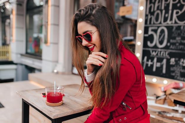 Wunderbares brünettes mädchen in der roten aufstellung mit schüchternem lächeln im straßencafé