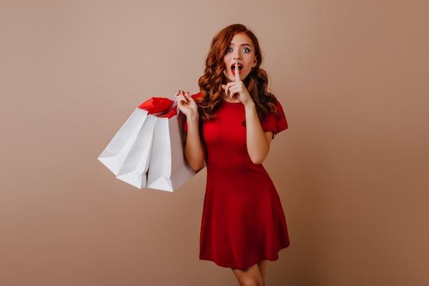 Wunderbares europäisches mädchen, das mit überraschtem lächeln nach dem einkaufen aufwirft. freudige ingwerdame, die geschäftstaschen hält.