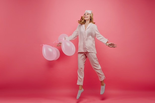 Wunderbares geburtstagskind in den niedlichen socken, die am morgen springen. indoor-foto in voller länge des aufgeregten weiblichen modells im pyjama, der vor der party herumalbert.
