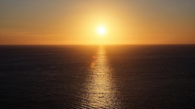 Wunderbares hellgelbes sonnenlicht, das sich in einem ruhigen, endlosen ozean widerspiegelt, der am abend einen sonnenpfad unter klarem himmel mit orangefarbener scheibe bildet