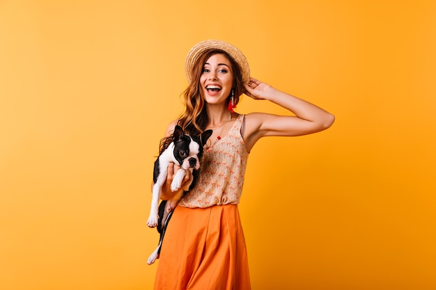 Wunderbares ingwermädchen im sommerhut, der glück während des porträtschießens mit hund ausdrückt. erstaunliches hübsches mädchen, das bulldogge hält und lächelt.