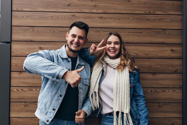Wunderbares junges paar, das positive gefühle während des gemeinsamen fotoshootings ausdrückt. innenporträt des lachenden mannes und der lachenden frau lokalisiert auf holzwand.