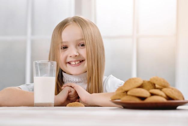 Wunderbares kleines mädchen mit süßem lächeln sitzt in der nähe von keksen