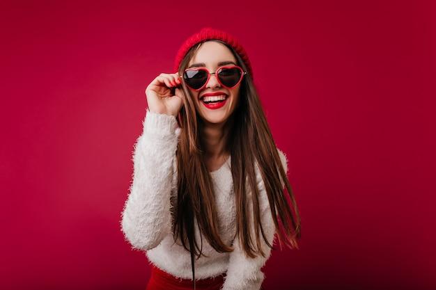 Wunderbares mädchen in der trendigen herzbrille, die gute gefühle ausdrückt
