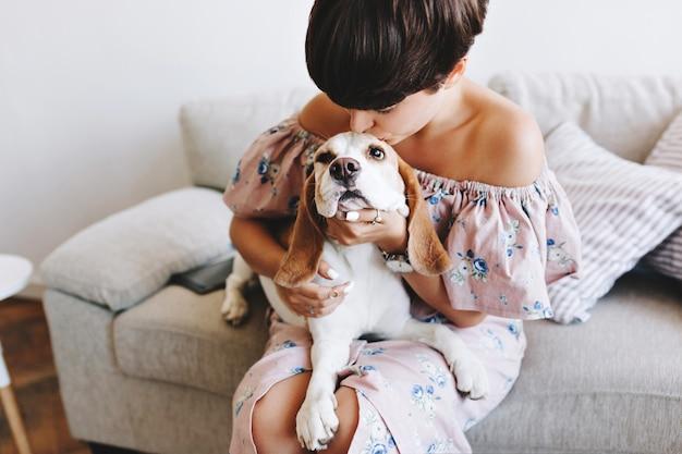 Wunderbares mädchen mit der trendigen kurzen frisur, die beagle-hund küsst, während sie auf grauem sofa sitzt