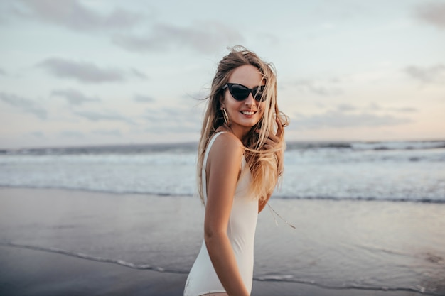 Wunderbares mädchen mit hellbraunem haar, das über die schulter schaut, während am ozean kühlt. foto der romantischen dame in der weißen badebekleidung, die seelandschaft am wochenende genießt.
