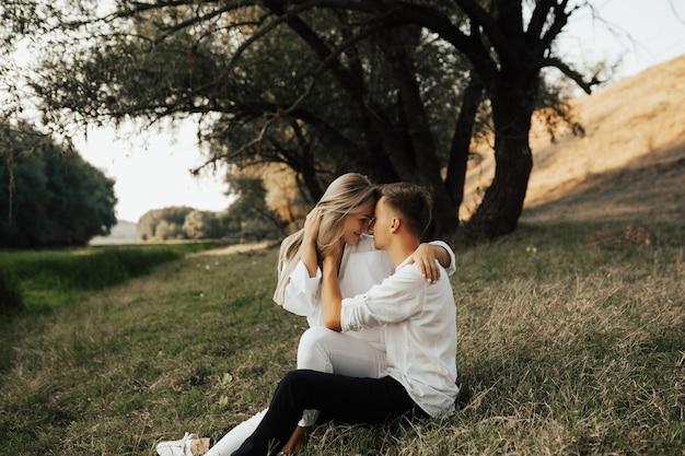 Wunderbares paar, das auf grünem gras im sommerpark sitzt und einander mit zärtlichkeit ansieht.