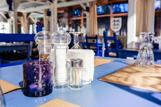 Wunderbares restaurant im loftstil. regale mit geschirr und ausrüstung. tische bereit für kunden. traditionelle mediterrane restaurant innenarchitektur. holzmöbel im restaurant. tabelle