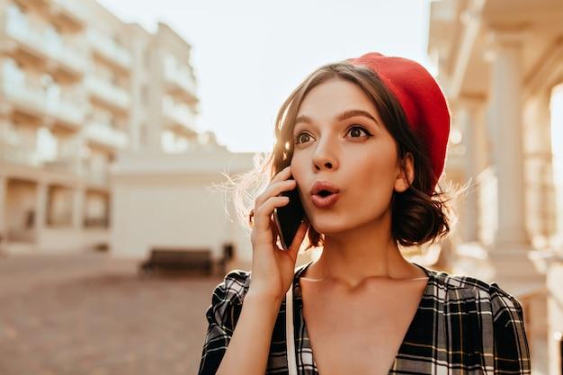 Wunderbares überraschtes mädchen im roten hut, das am telefon spricht. herrliche brünette dame mit smartphone, das im sonnigen herbsttag aufwirft.