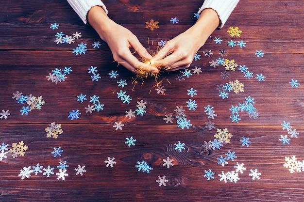 Wunderkerze in den weiblichen händen und in den dekorativen schneeflocken auf dem tisch