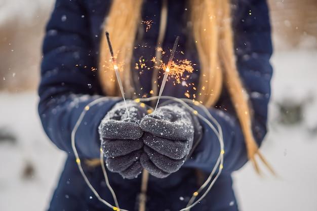 Wunderkerzen in den weiblichen händen auf einem hintergrund des schneefalls. weihnachts- und neujahrskonzept.