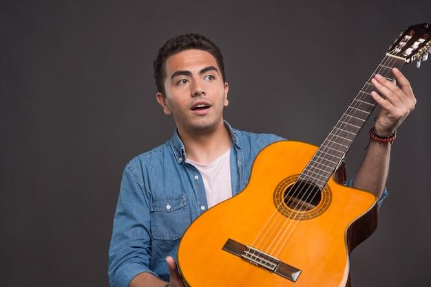 Wundernder mann, der die gitarre auf schwarzem hintergrund hält. hochwertiges foto