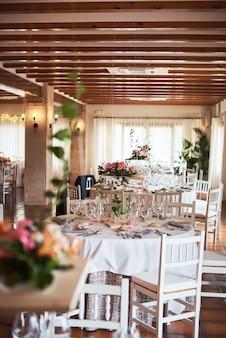 Wunderschön dekorierte tische für gäste mit dekorationen in einem restaurant.