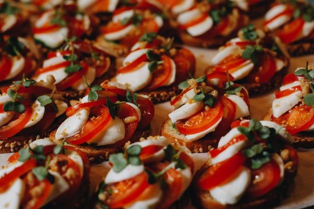Wunderschön dekorierter catering-banketttisch mit verschiedenen snacks und vorspeisen mit sandwich, kaviar und frischem obst.