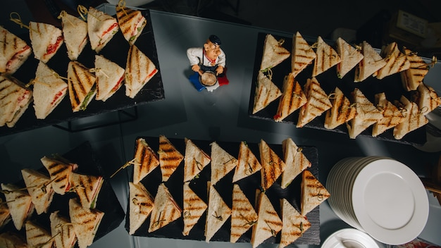 Wunderschön dekorierter catering-banketttisch mit verschiedenen snacks und vorspeisen mit sandwich