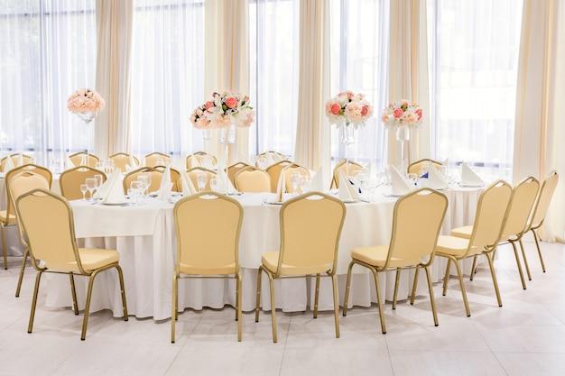 Wunderschön eingerichtetes zimmer mit gedeckten tischen mit blumen im restaurant
