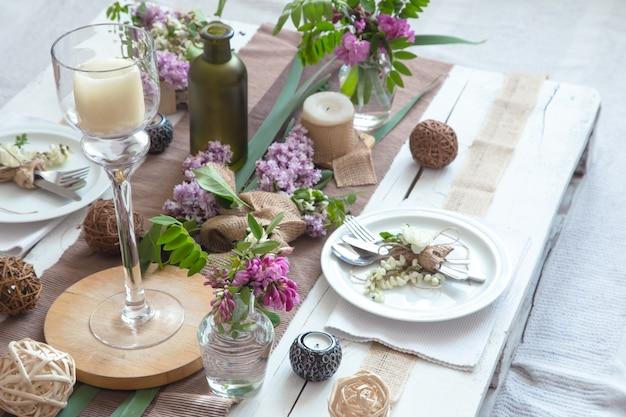 Wunderschön elegant dekorierter tisch für den urlaub - hochzeit oder valentinstag mit modernem besteck, schleife, glas, kerze und geschenk