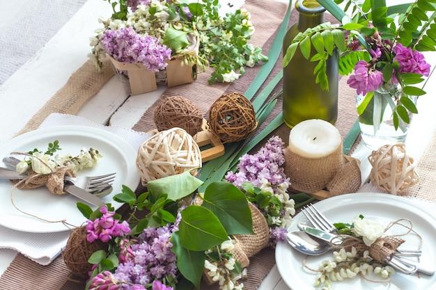 Wunderschön elegant dekorierter tisch für den urlaub mit frühlingsblumen und grüns - hochzeit oder valentinstag mit modernem besteck, schleife, glas, kerze und geschenk, horizontal, nahaufnahme, getönt