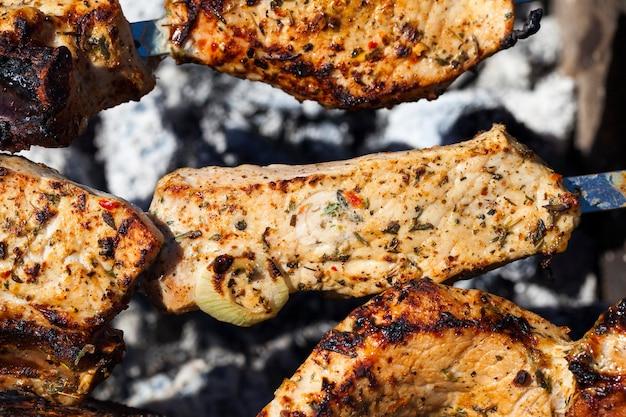 Wunderschön geröstetes schweinefleisch auf dem grill in flammen, während eines picknicks