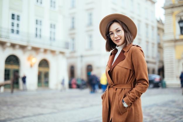 Wunderschön im modernen braunen mantel, der auf straße im stadtzentrum aufwirft
