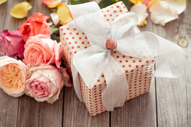 Wunderschön verpackte geschenkbox und frische rosen zum valentinstag oder frauentag. urlaubskonzept.