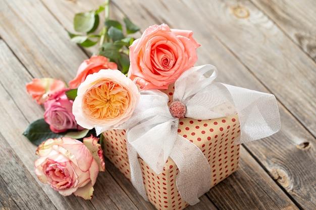 Wunderschön verpacktes geschenk und ein strauß rosen auf einem unscharfen hölzernen hintergrund.