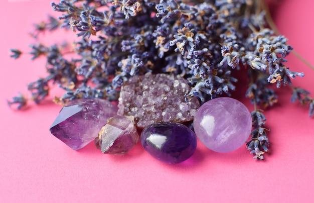 Wunderschöne amethystkristalle und runder rosenquarzstein mit trockenem lavendelbouquet. magische amulette.