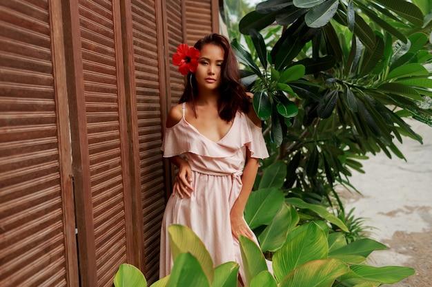Wunderschöne asiatische frau mit hibiskusblume in den haaren, die über holzwand aufwerfen.