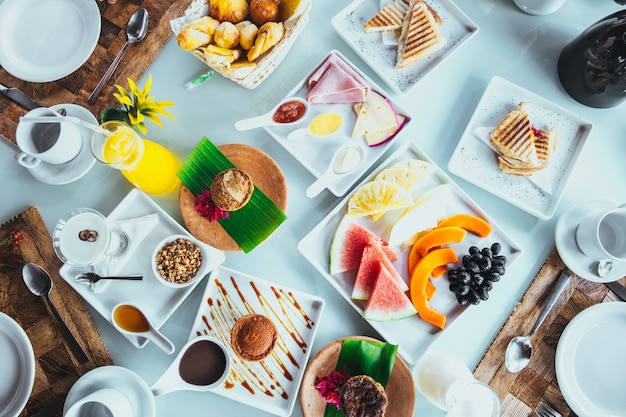 Wunderschöne auswahl an speisen zum frühstück, die in einem tropischen resort auf weißen gerichten serviert werden
