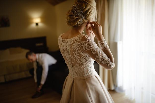 Wunderschöne, blonde braut in einem weißen luxuskleid, das sich für die hochzeit fertig macht