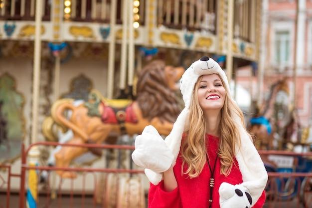 Wunderschöne blonde frau mit rotem strickpullover und lustigem hut, die im hintergrund des karussells mit lichtern posiert